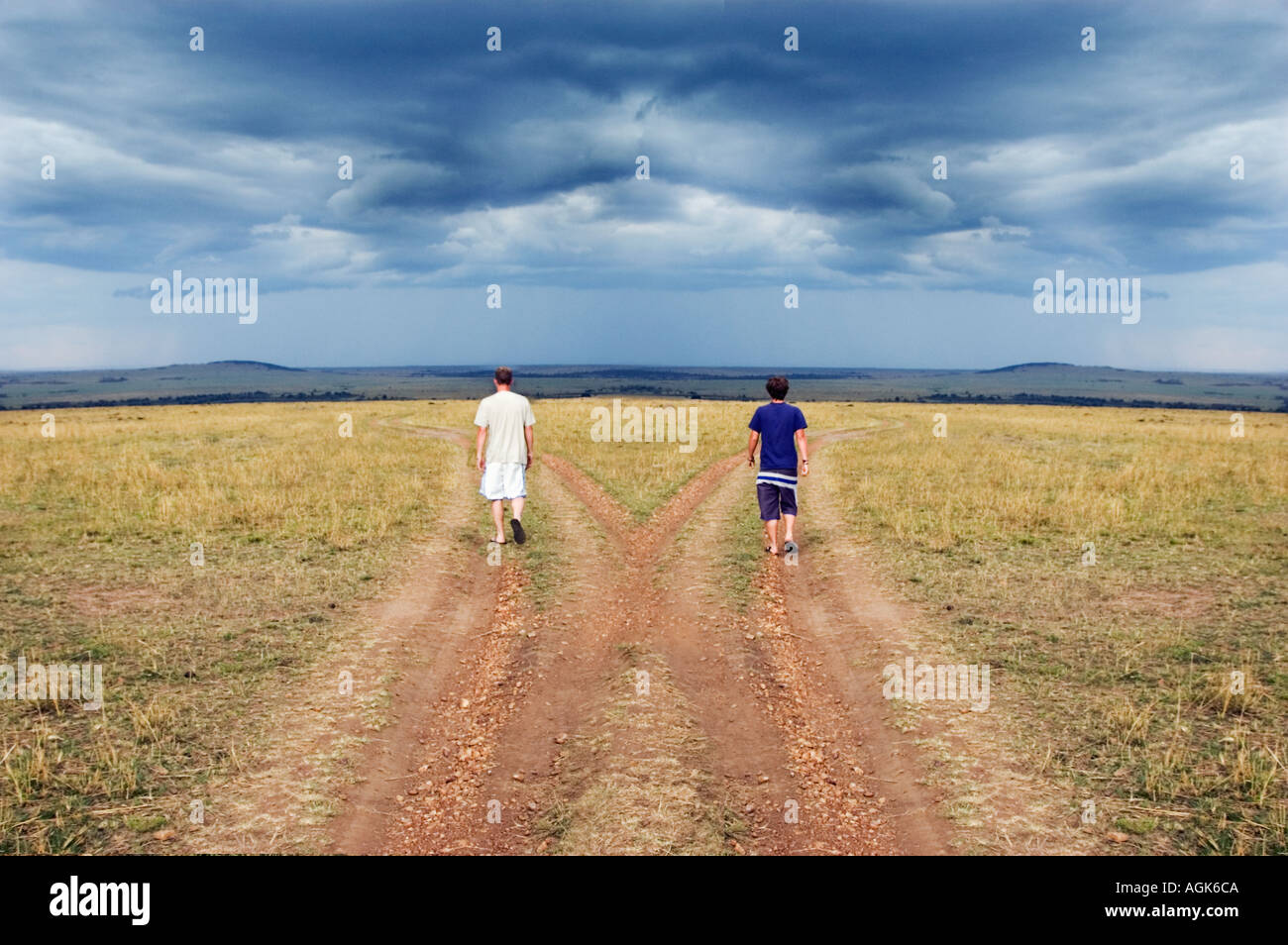 Two young men walking down different paths Stock Photo ...