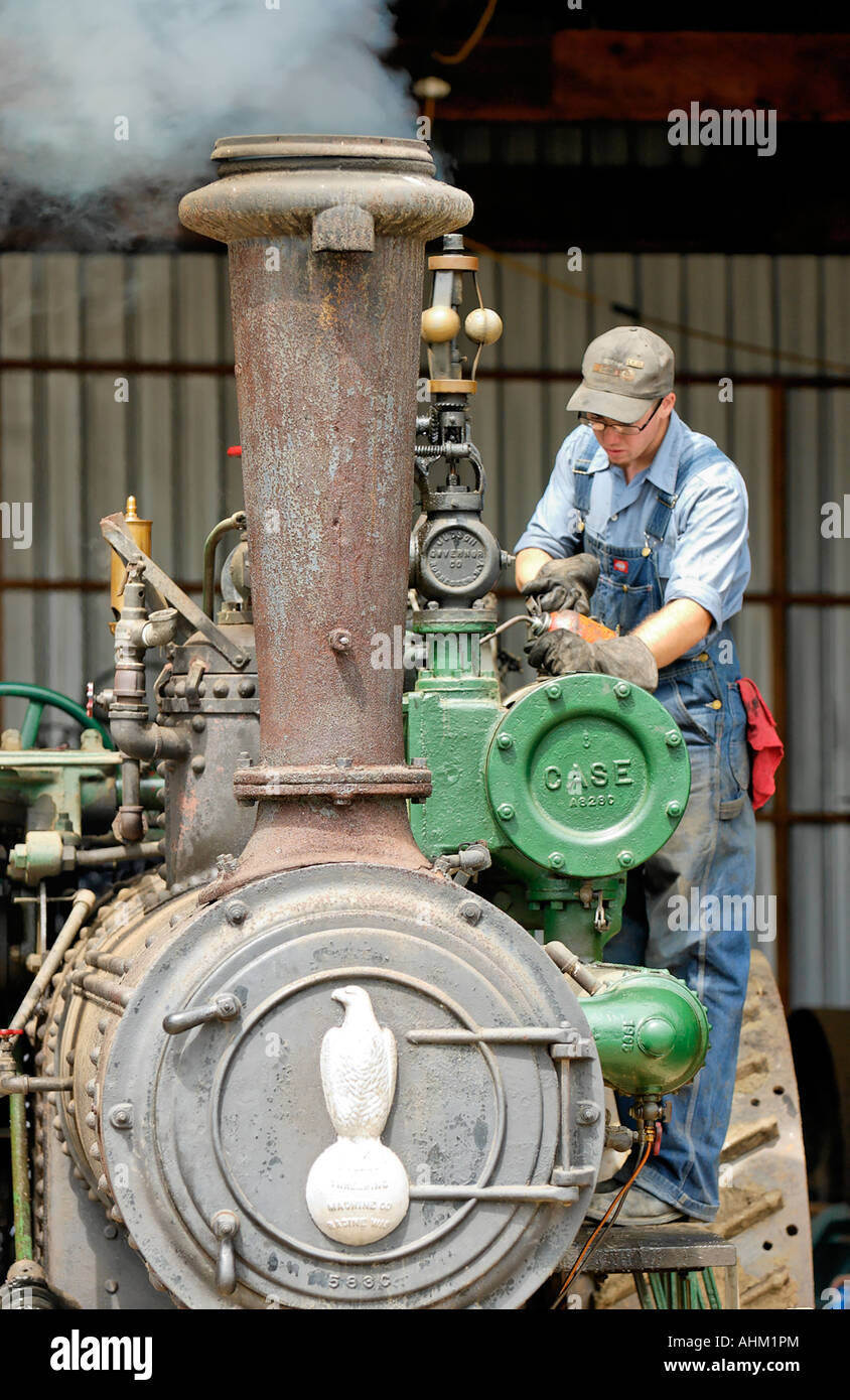 Guy Fixing Tractor : Man working on old steam tractor antique gas and