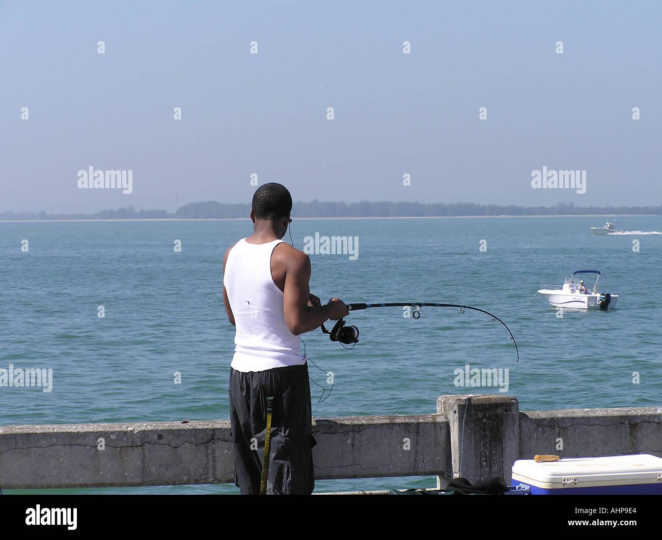 Black man fishing from pier near skyway bridge in st for Free fishing piers near me