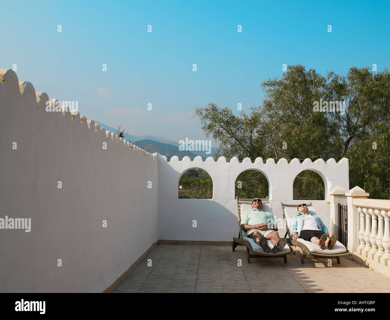 Senior couple sunbathing on balcony terrace stock photo for Balcony sunbathing
