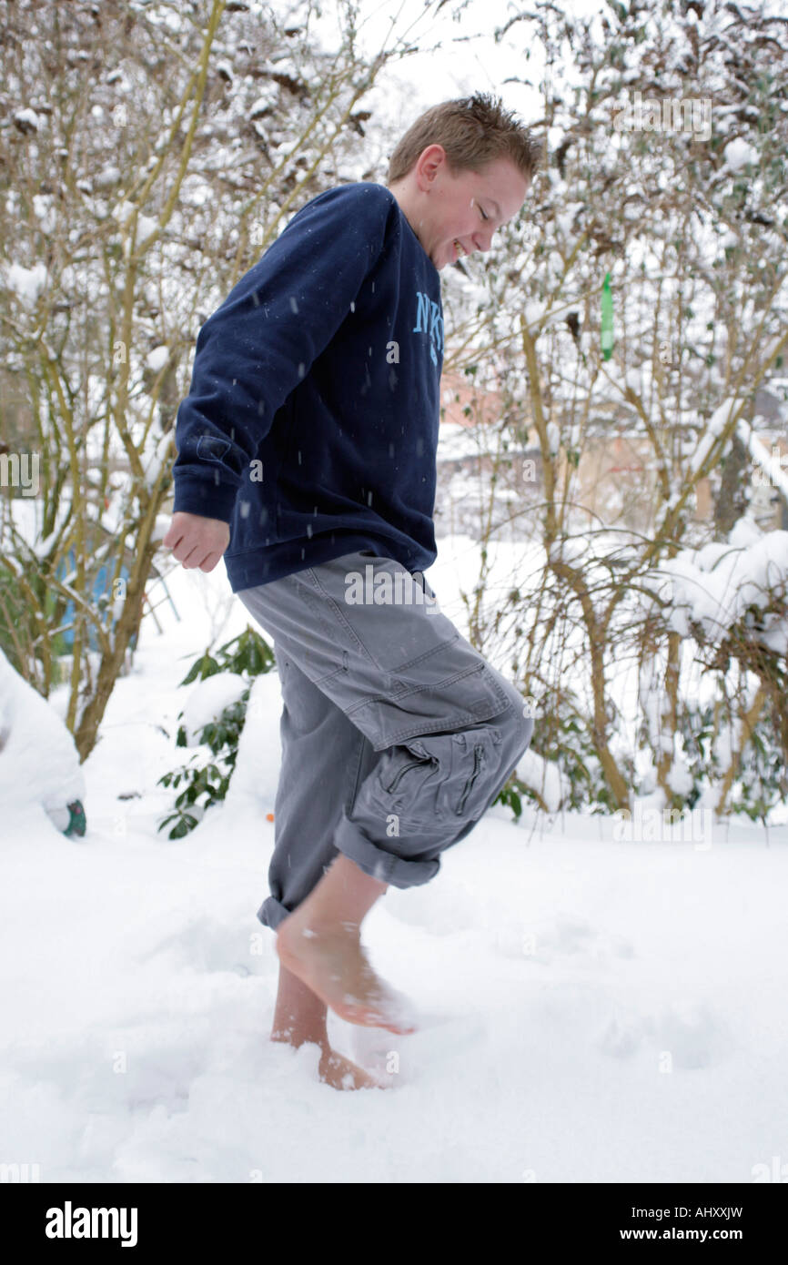 Young Boy Walking Barefoot In Snow Stock Photo, Royalty