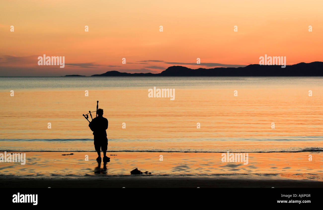 a-bagpiper-silhouetted-against-the-sunset-on-arisaig-beach-in-the-AJ6PGR.jpg
