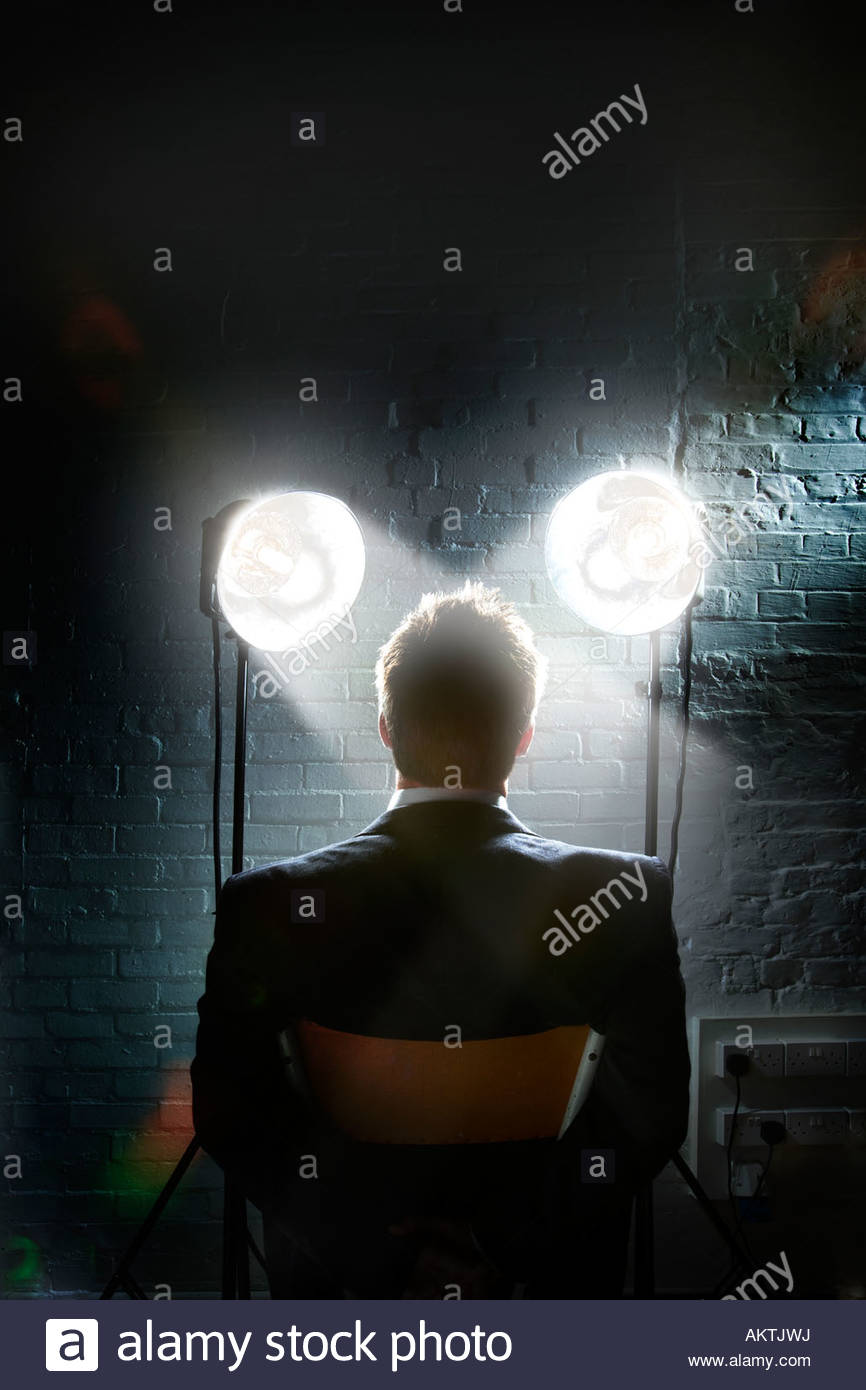 Interrogation scene with spotlights shining in a man's face - back view of restrained businessman Stock Foto