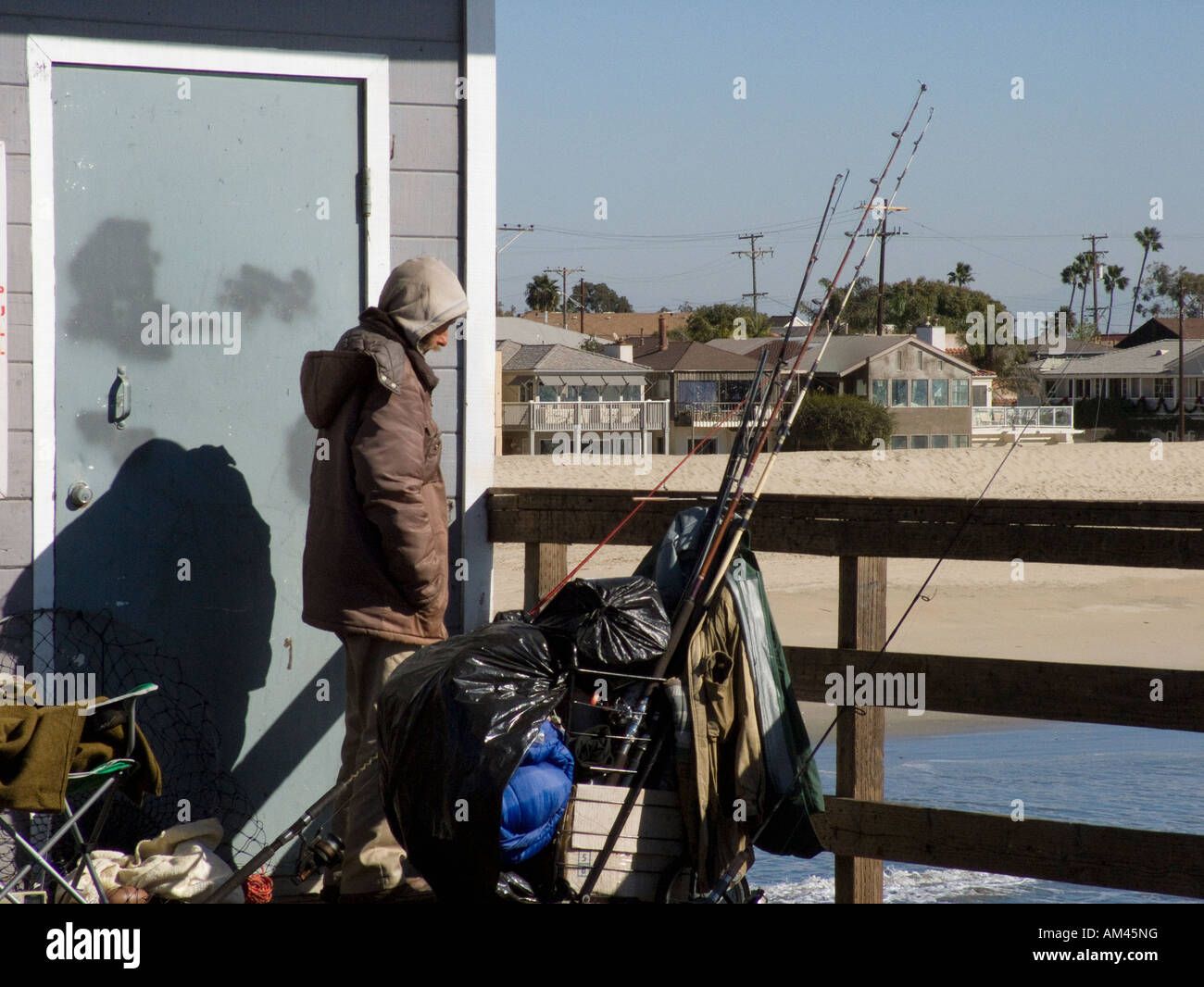 Homeless man fishing from the seal beach pier in seal for Seal beach fishing