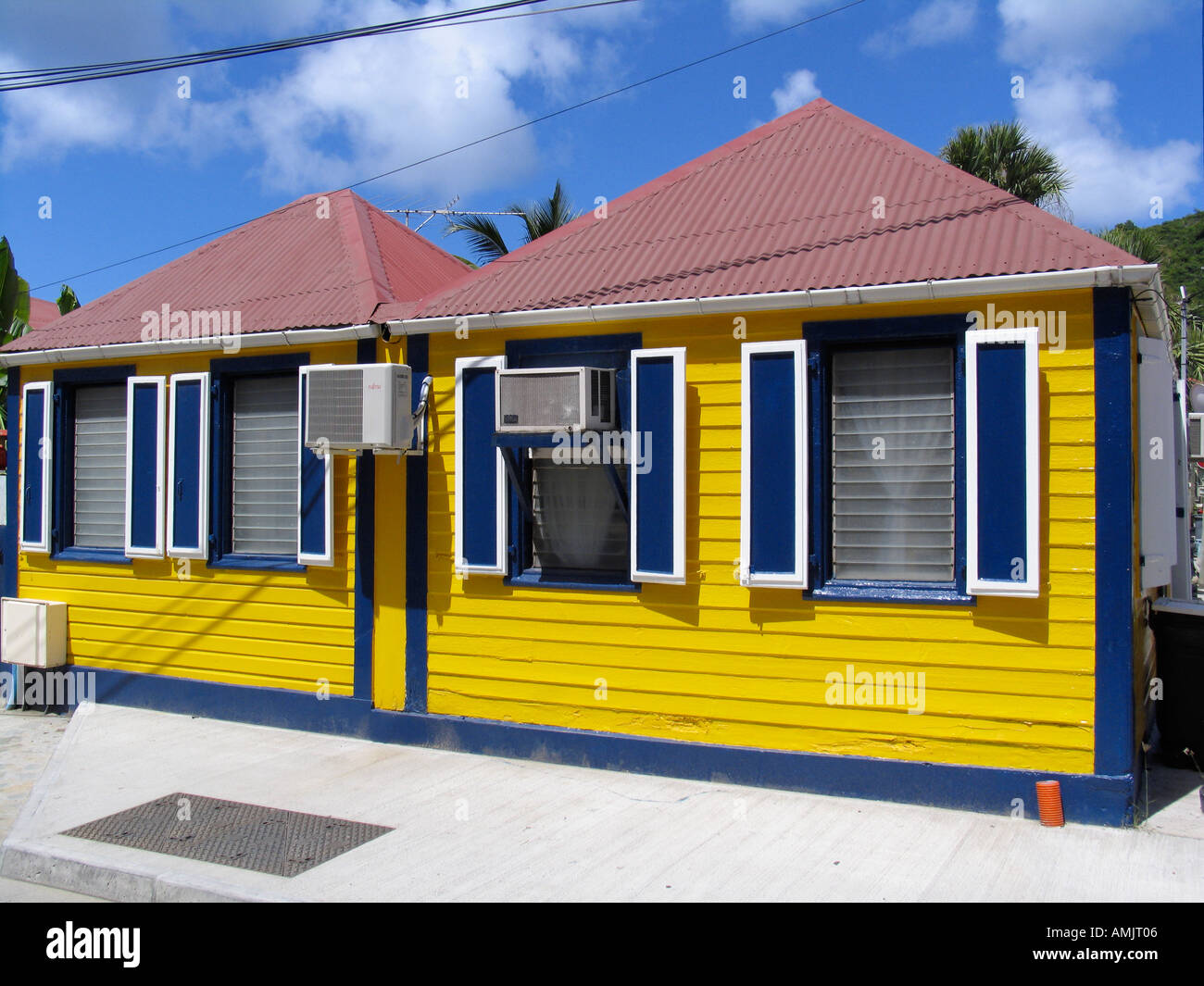 Bright yellow wooden house with red tin roof blue shutters for Yellow and red house