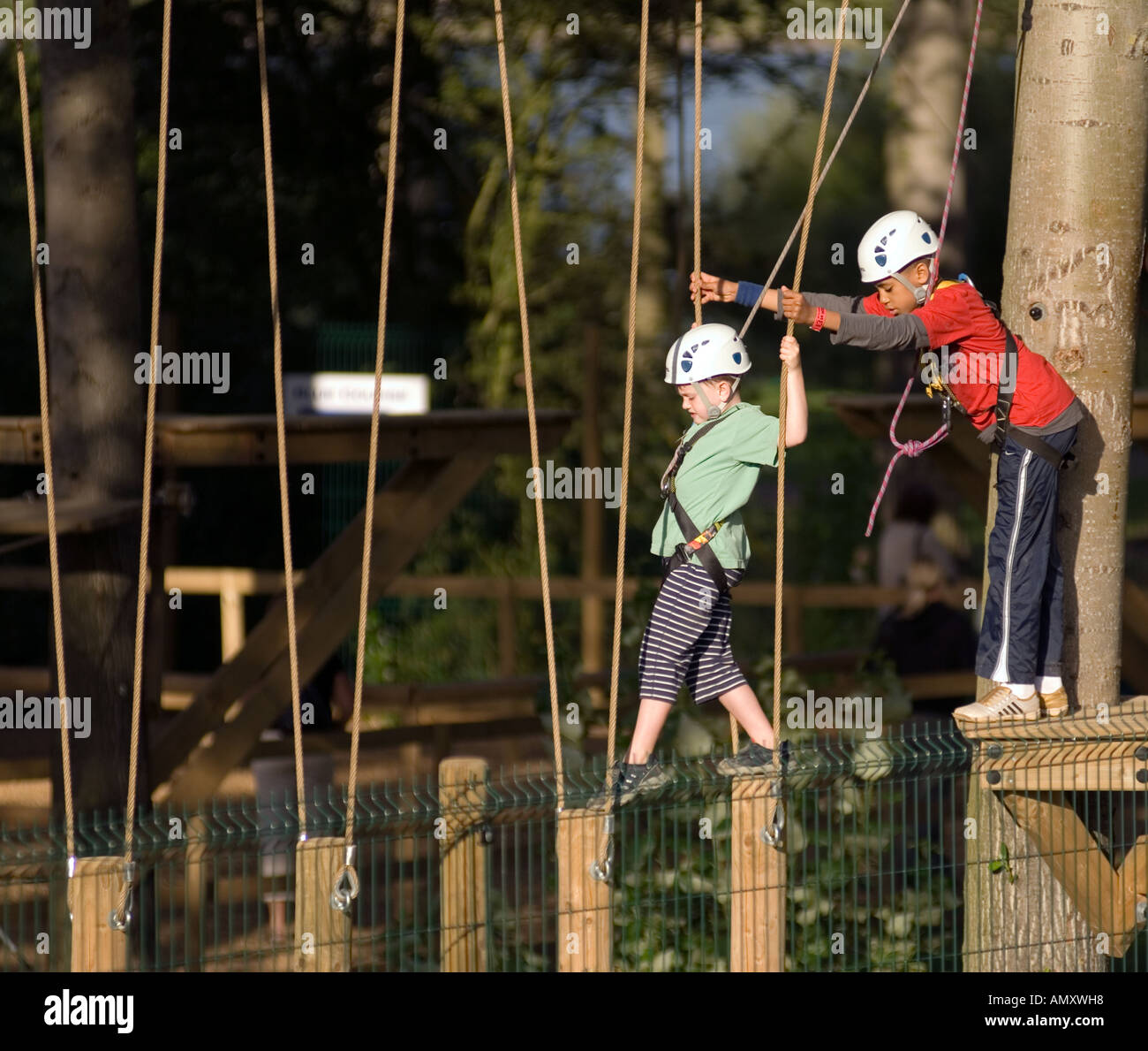 PICTURE CREDIT DOUG BLANE Young boy being helped across a log bridge at the Aerial Extreme Willen Lake Milton Keynes Stock Photo