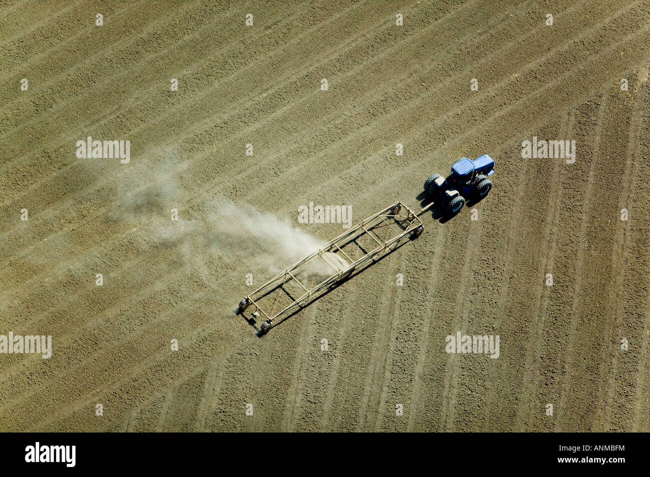 aerial above a tractor plowing a field in California Central Valley Stock Photo