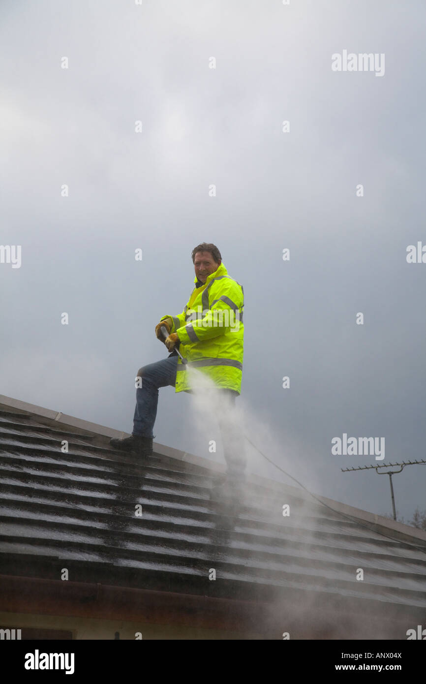 A man cleaning the roof of a house using a high pressure water jet stock photo royalty free - Using water pressure roof cleaning ...