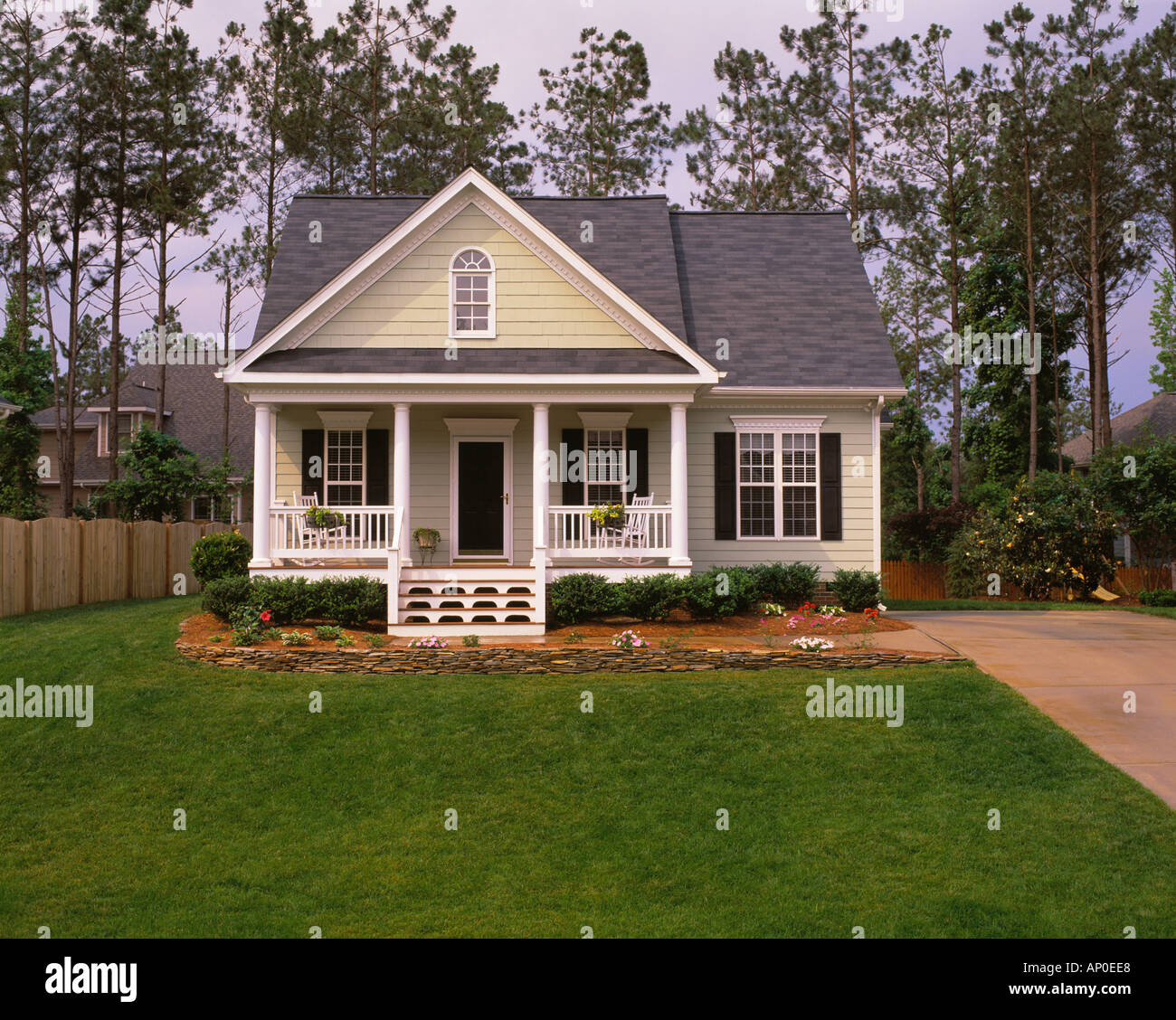 Small Tan House With Black Shutters White Trim And A Large