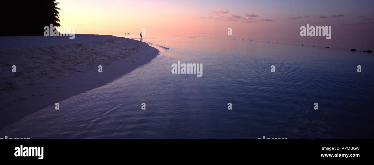 panoramic-view-of-figure-on-a-tropical-island-beach-at-sunset-in-the-APMBGW.jpg