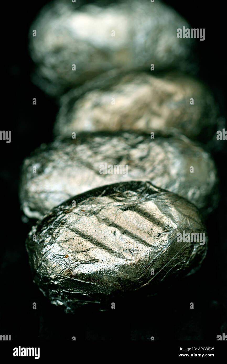 Potatoes wrapped in aluminium sizzling on the BBQ Stock Photo