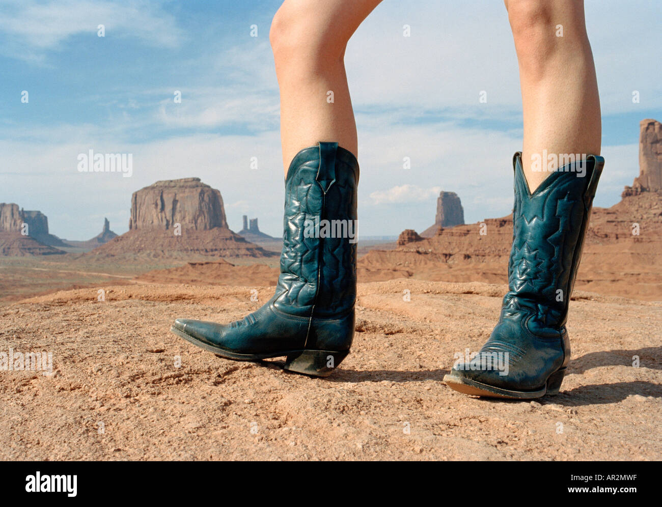 Woman standing in desert wearing cowboy boots Stock Photo ...
