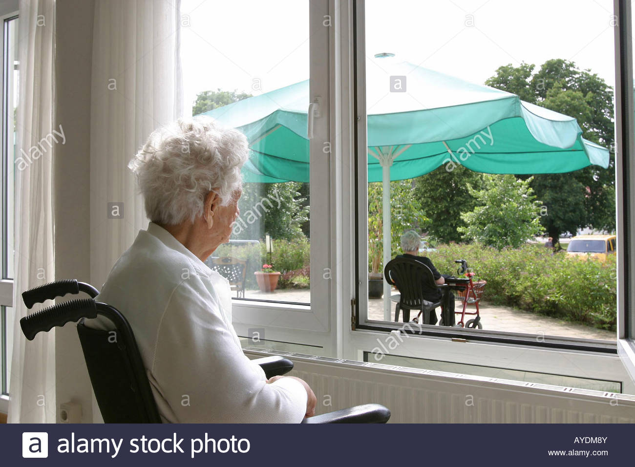 Old woman on a wheelchair looking through a window Stock Foto