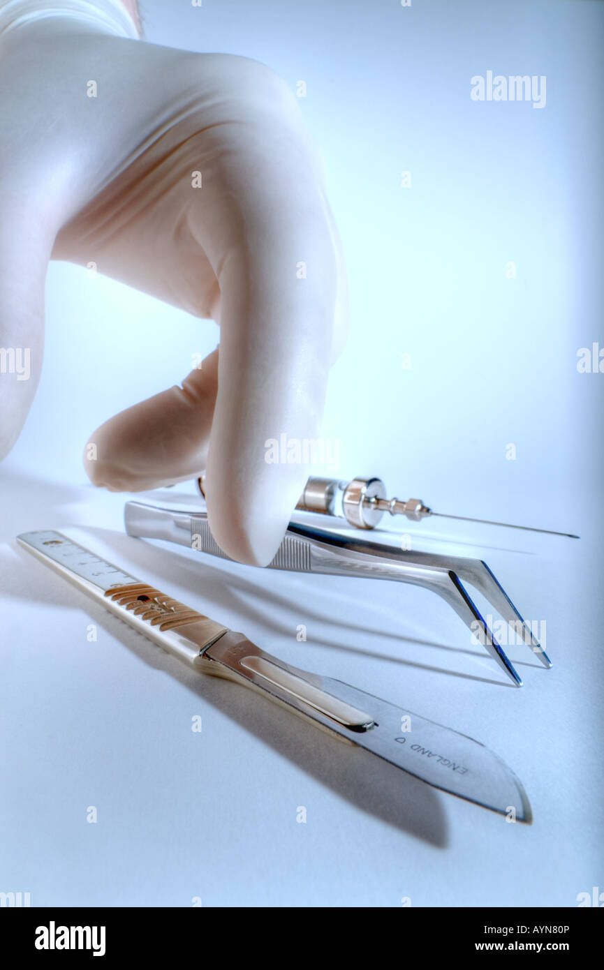 Hand picking up scalpel Stock Photo