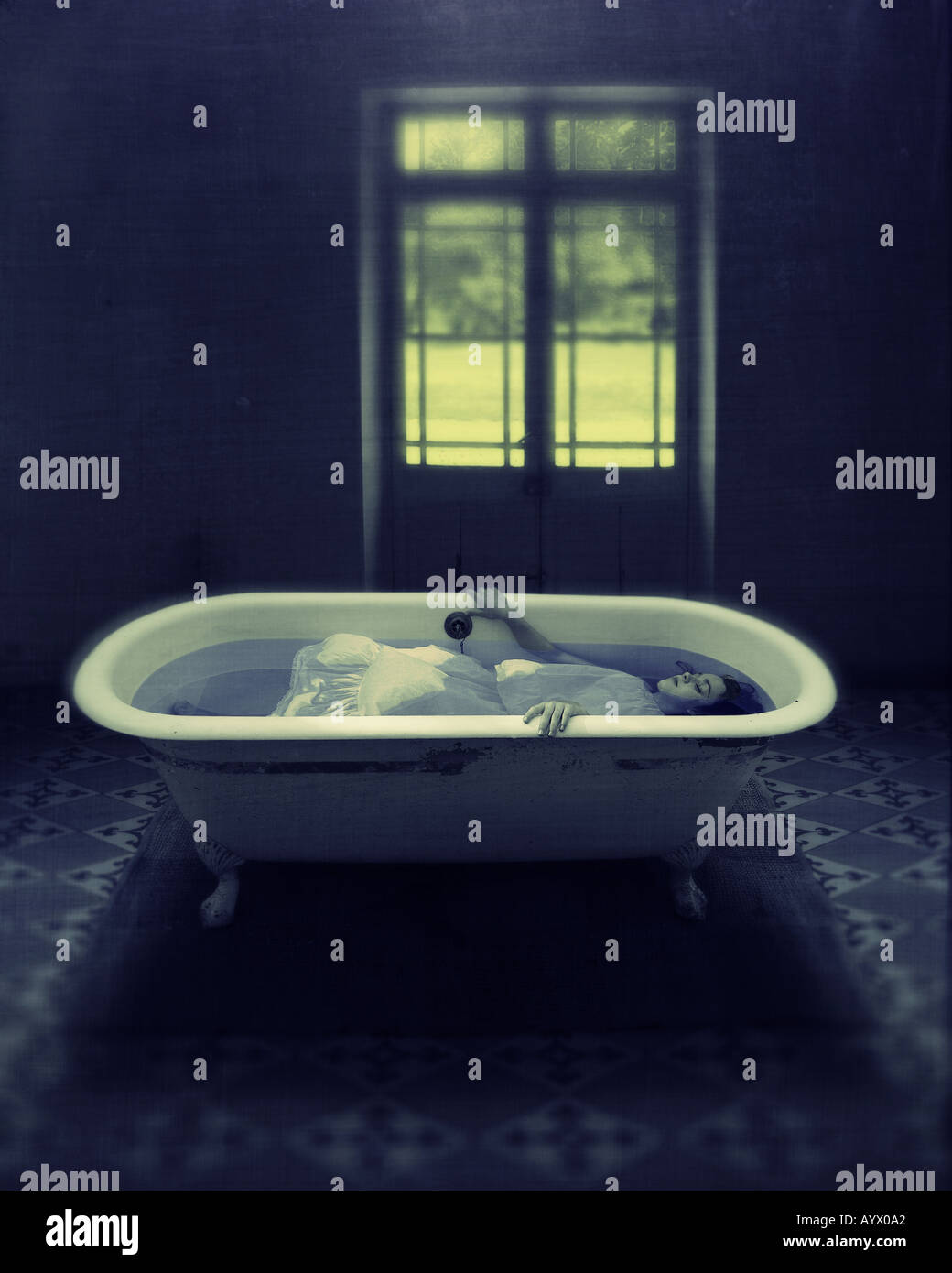 girl in white dress immersed in water in bathtub in empty room with door to garden Stock Foto