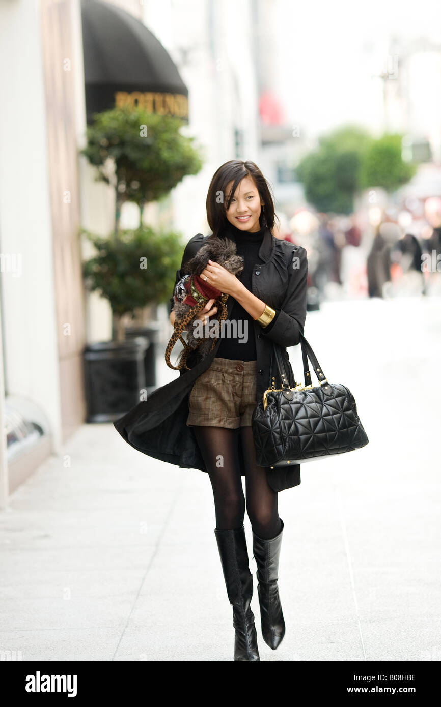 A young woman is walking through a crowded city street holding a canine companion. Stock Photo