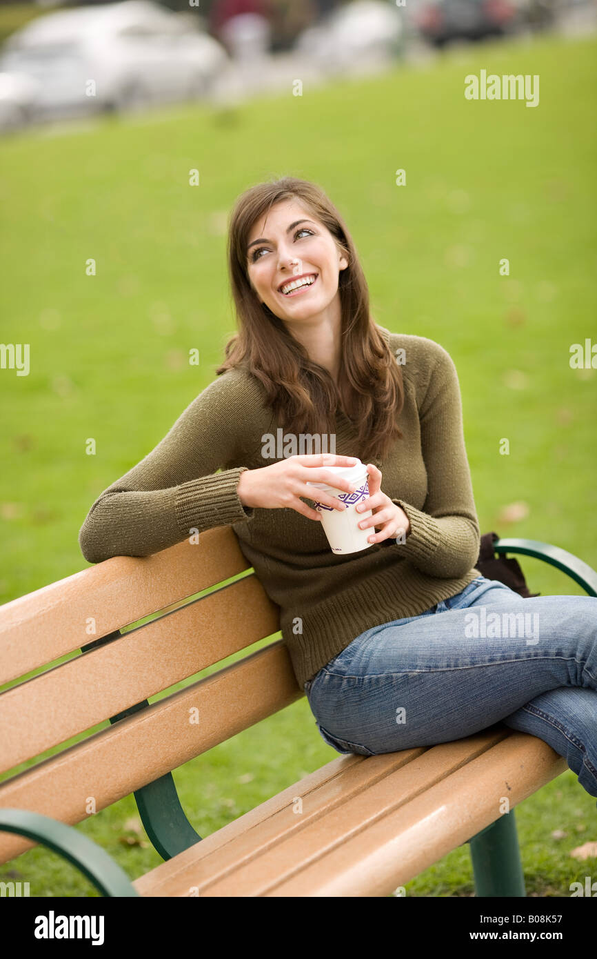 A woman is smiling while sitting on a park bench holding a drink Stock Photo