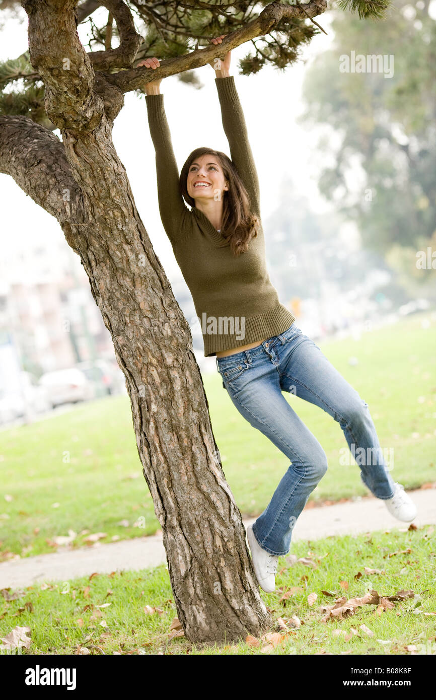 A woman jumping for joy, laughing, smiling in a park and playfully swinging from a tree limb. Stock Photo