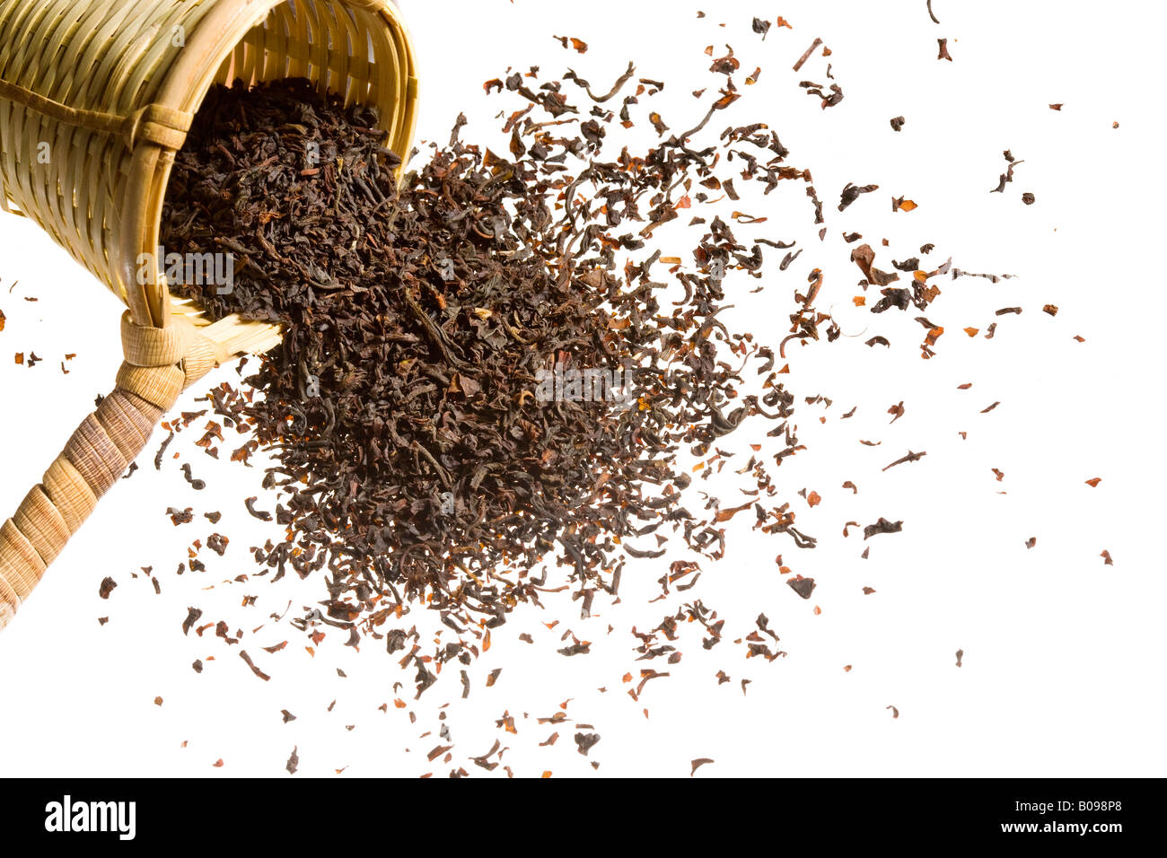 An overflowing heap of raw tea spilling out of a woven scooper. Stock Photo