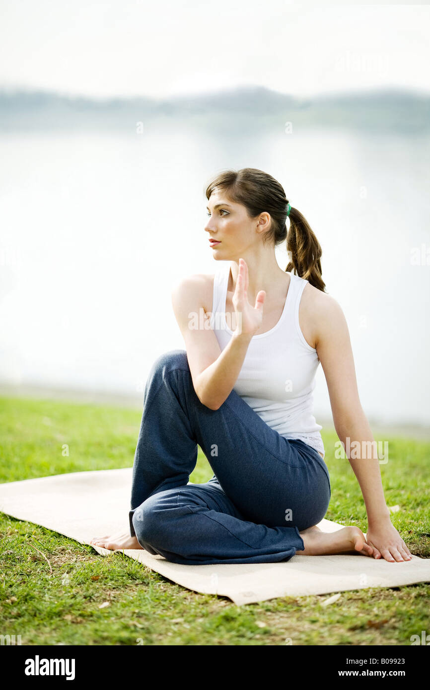 A young woman is practicing yoga in a park near a lake. Stock Photo