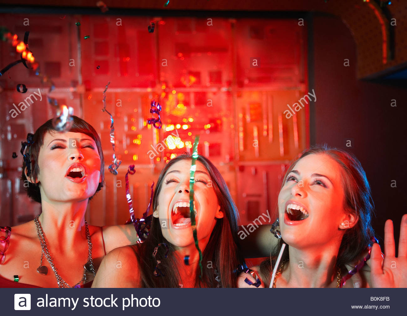Three women in a nightclub drinking and laughing Stock Foto