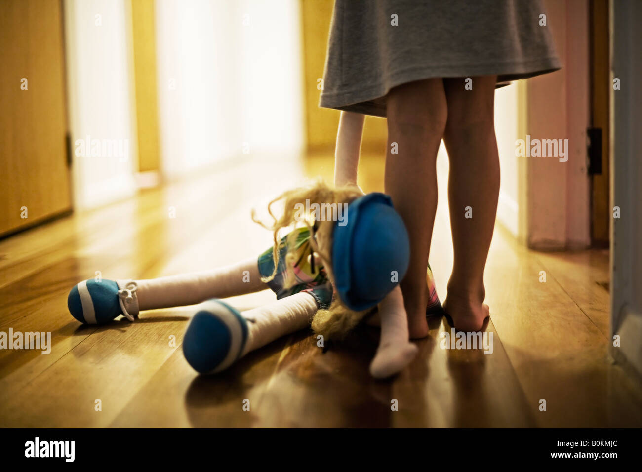 Girl aged four carries toy doll in hall Stock Foto