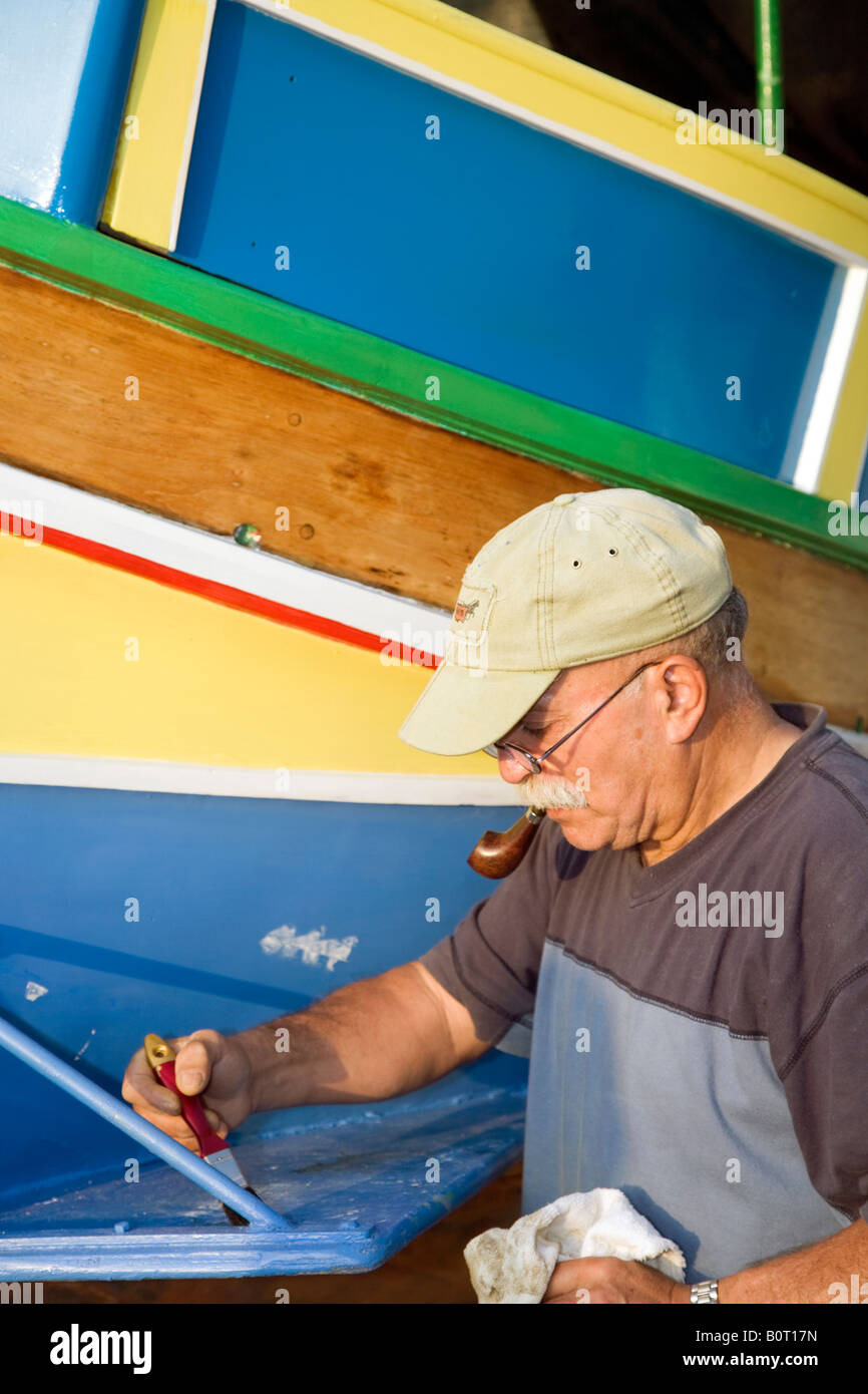 Man repainting a LuzzuA Traditional Maltese foreign fishing boats Stock Foto
