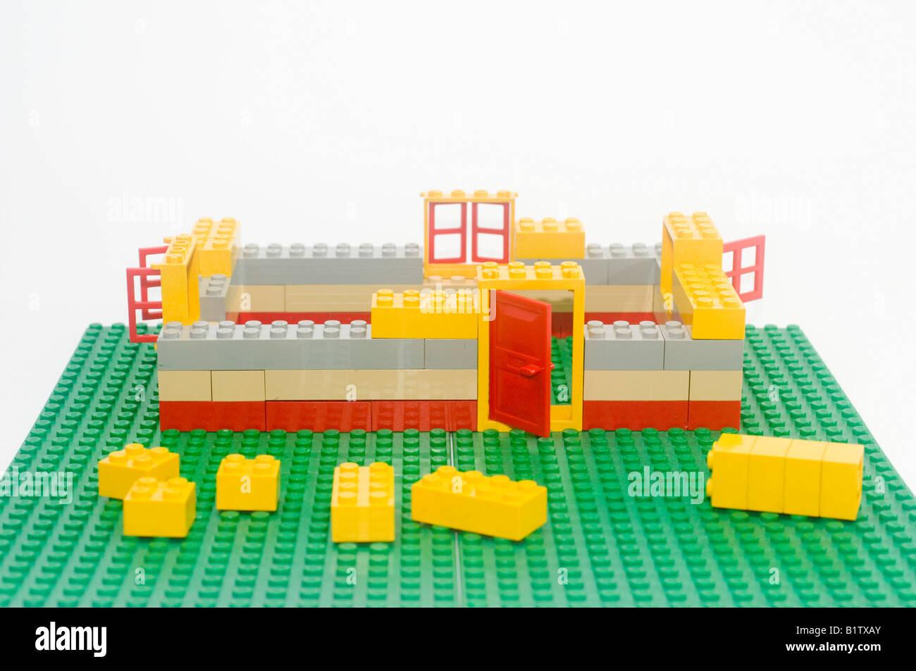 Lego House construction process on white background Stock ...