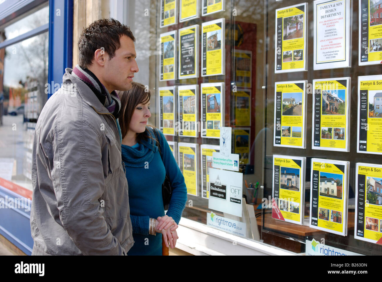A young couple aspiring to buy their first home browse the listings in an estate agency window Stock Photo