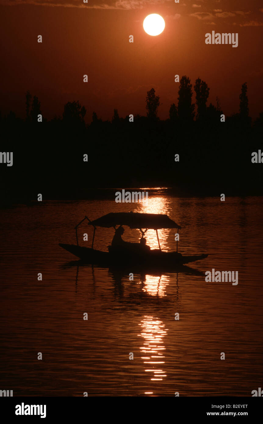 A couple floats in a shikara on Lake Dal in Srinagar India during sunset Stock Photo