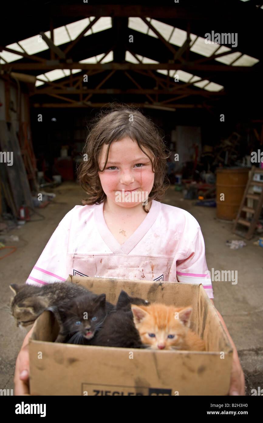 Young girl in rural Iowa, holding box of new kittens, Iowa, USA Stock Foto