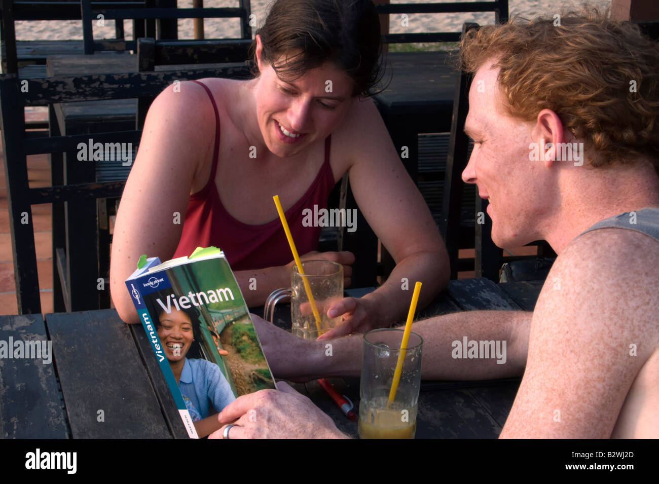Stock Photo - Young couple consult Lonely Planet Vietnam tour guide book Phu Quoc Island Vietnam