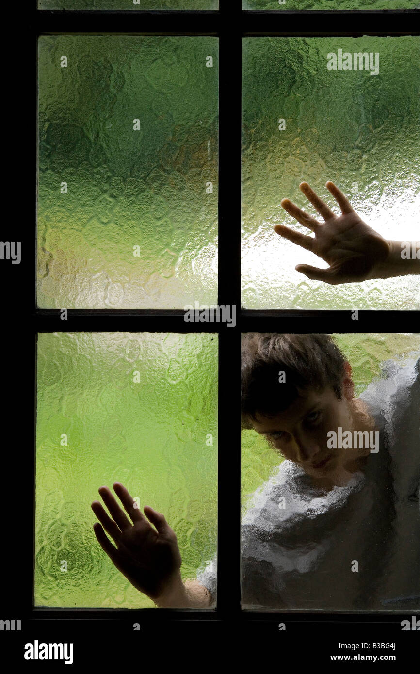 silhouette of person behind glass window with hands on panes of glass Stock Foto
