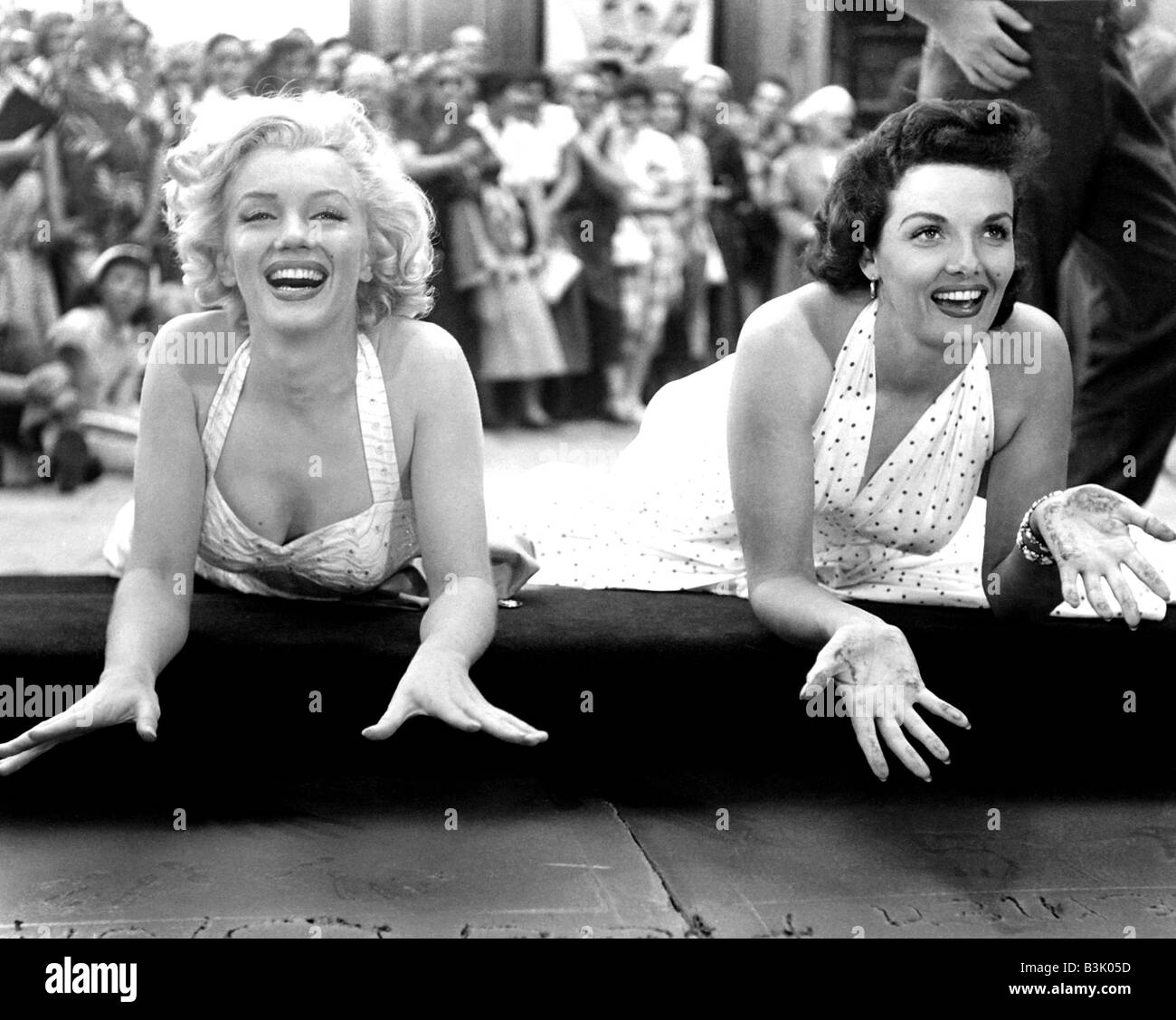MARILYN MONROE at left and Jane Russell leave their handprints at Graumann's Chinese Theatre in Hollywood in 1953 Stock Photo