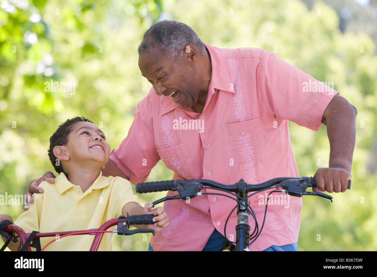 Grandfather and grandson on bikes outdoors smiling Stock Foto