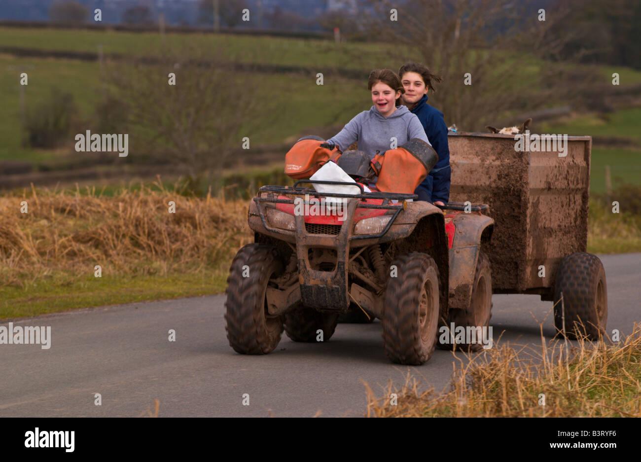 Two farm girls on quad bike with trailer on Mynydd Illtyd ...