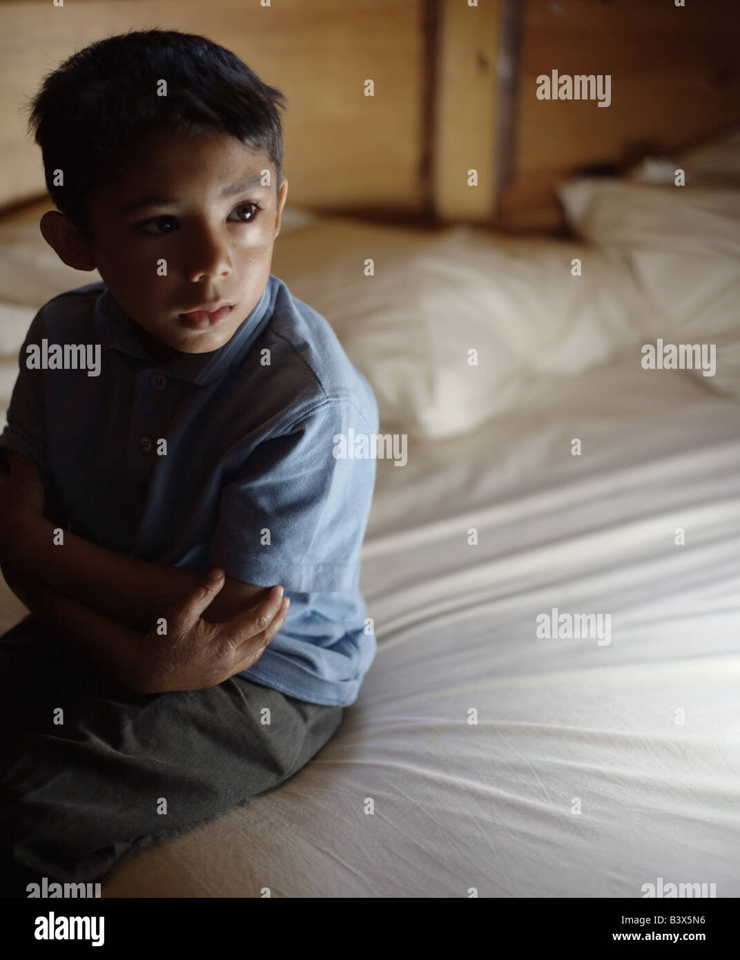 A five year old boy wearing a blue top and grey trousers sits on the edge a bed looking sad, lonely, abandoned and Stock Photo