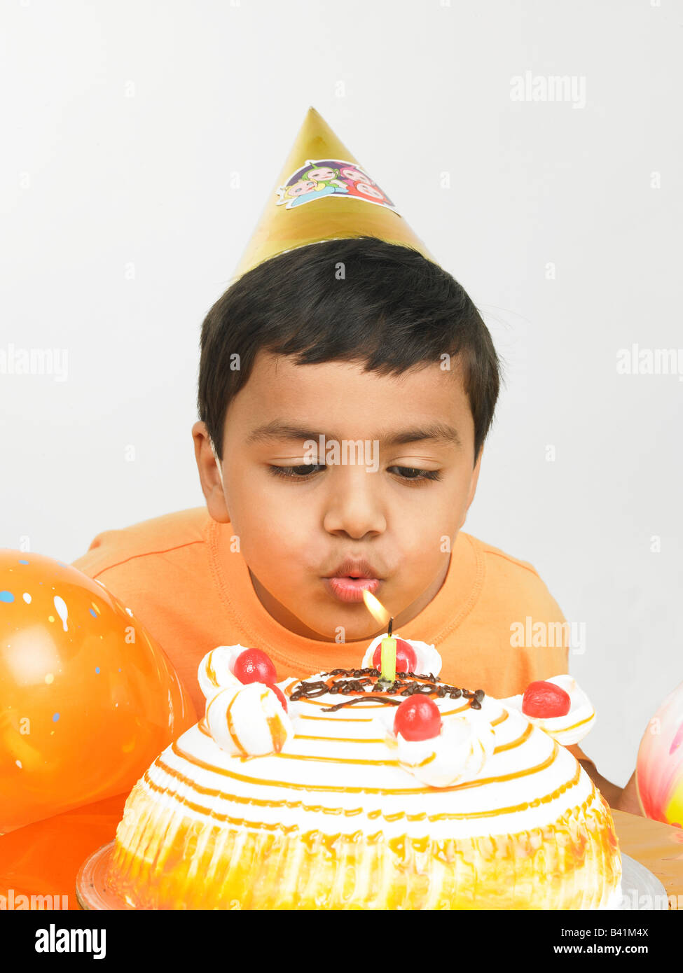 asian kid of indian origin blowing the candle of his birthday cake Stock Photo