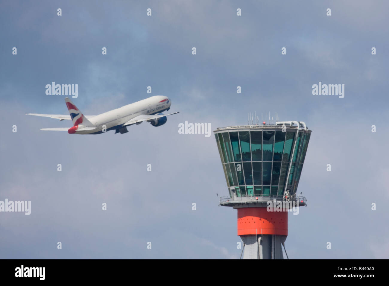 British Airways Boeing 777 taking off in the background of London Heathrow control tower. Stock Photo