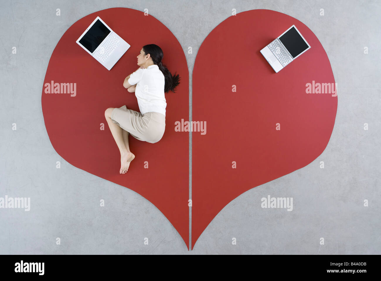 Woman lying on the ground with laptop on large broken heart, abandoned laptop behind her Stock Foto