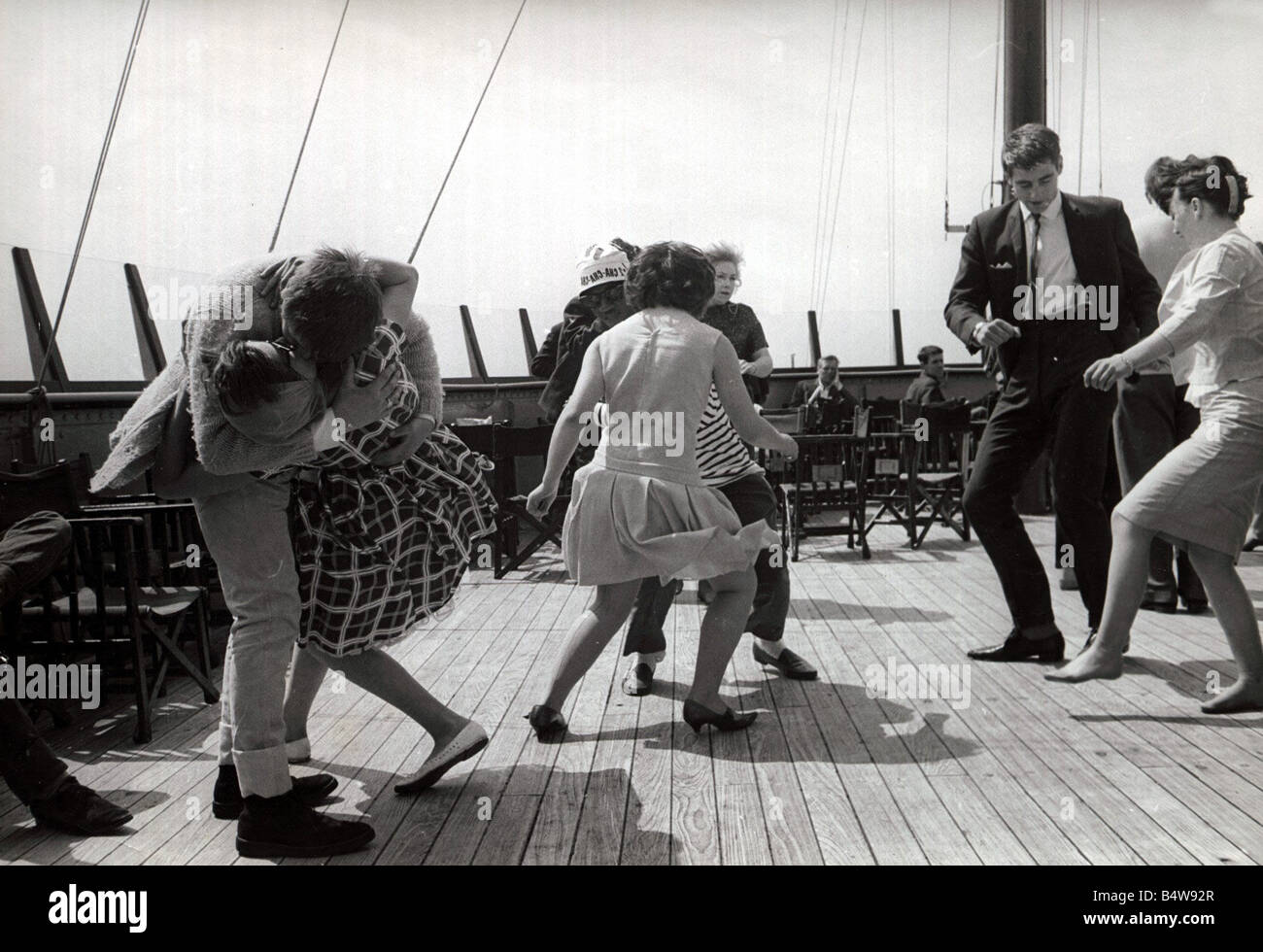 boat party couples dance and jive in true 60 s style Couple kissing doing the twist having fun humour ecard02 Stock Photo