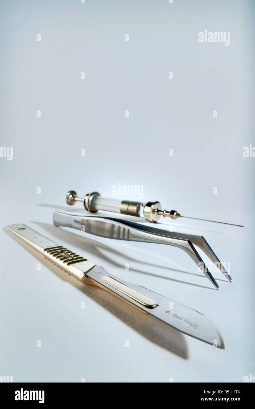 Scalpel, tweezers and a syringe Stock Photo