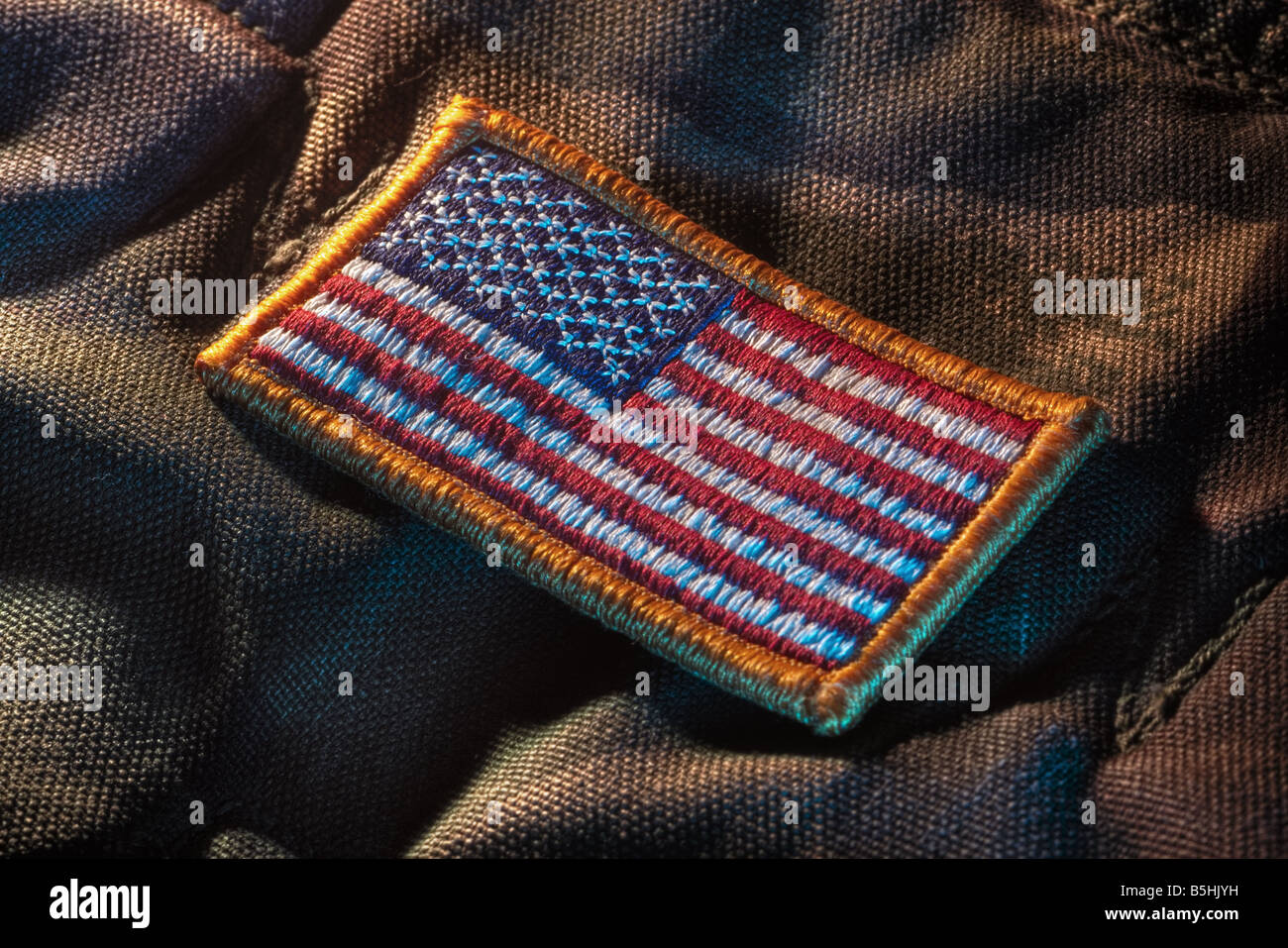 Detachable US flag patch on military camouflage fabric Stock Photo