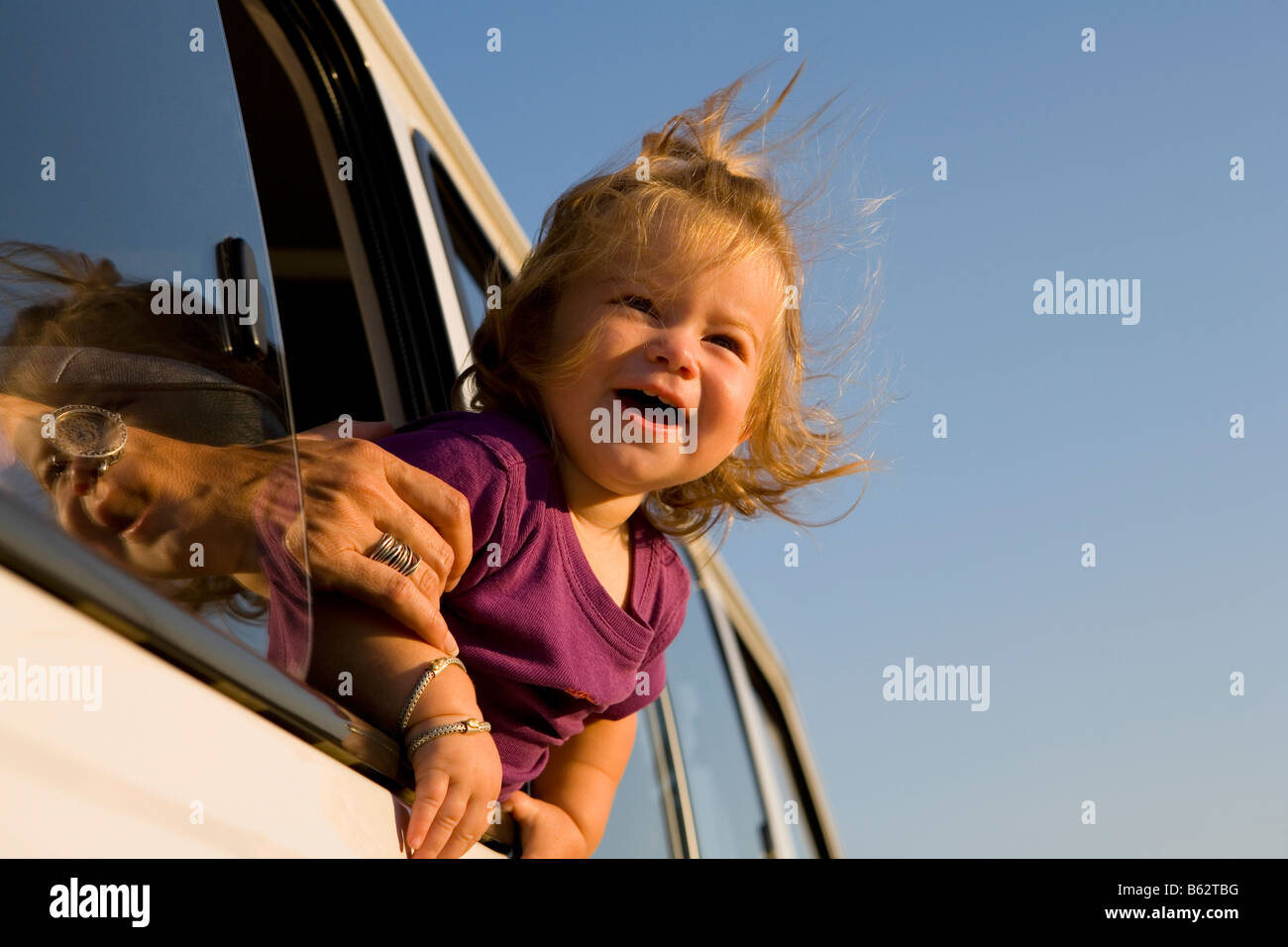 closeup of a baby girl looking out of a car window and