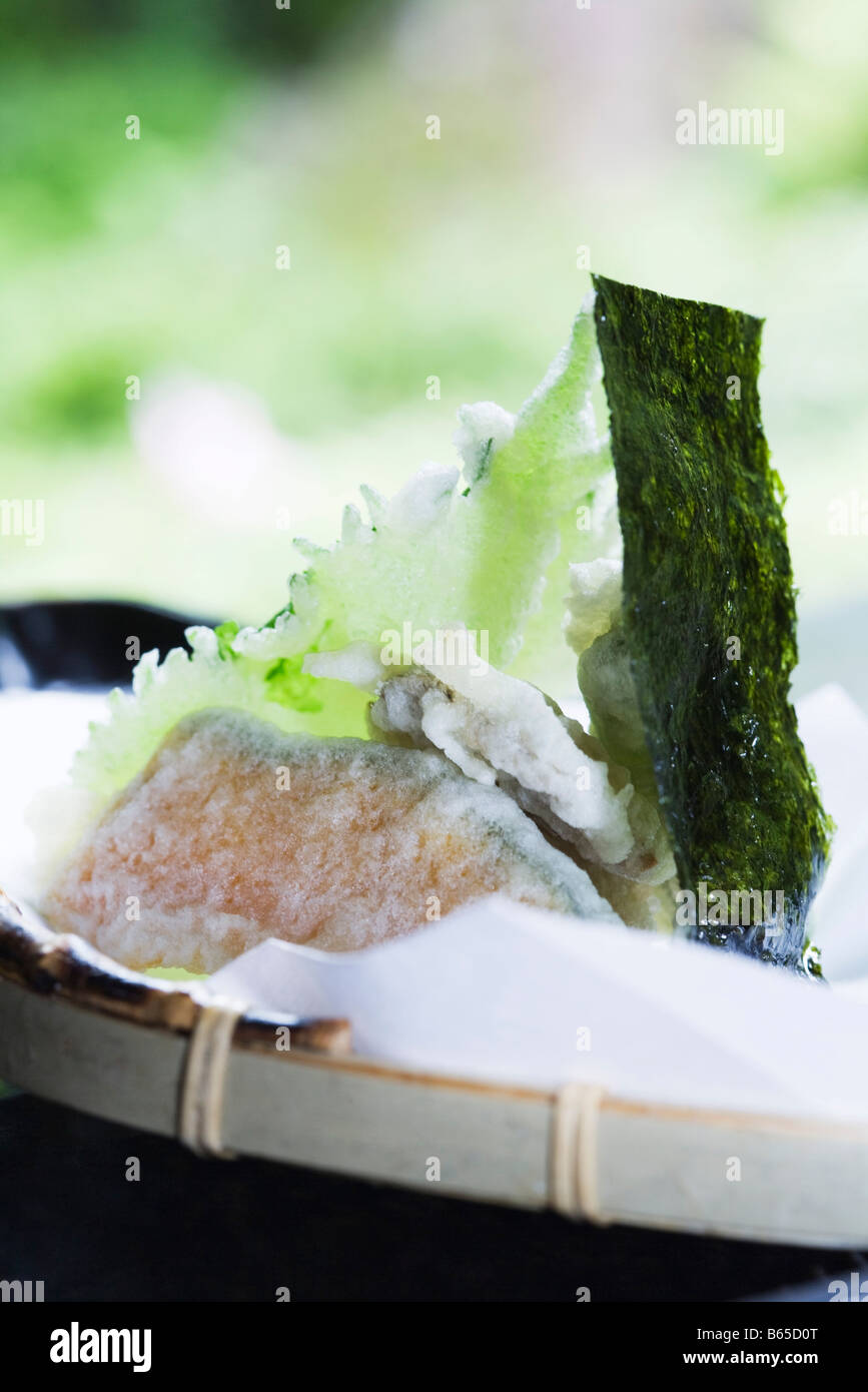 Winter squash and shiso tempura with piece of nori, close-up Stock Photo