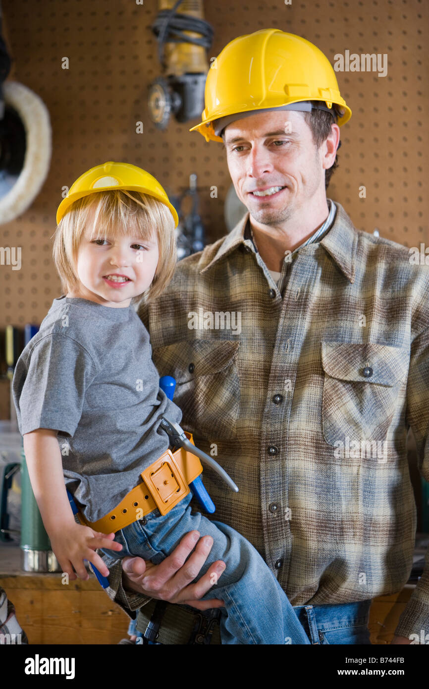 Portrait Of Father And Son In Garage Wearing Hard Hats