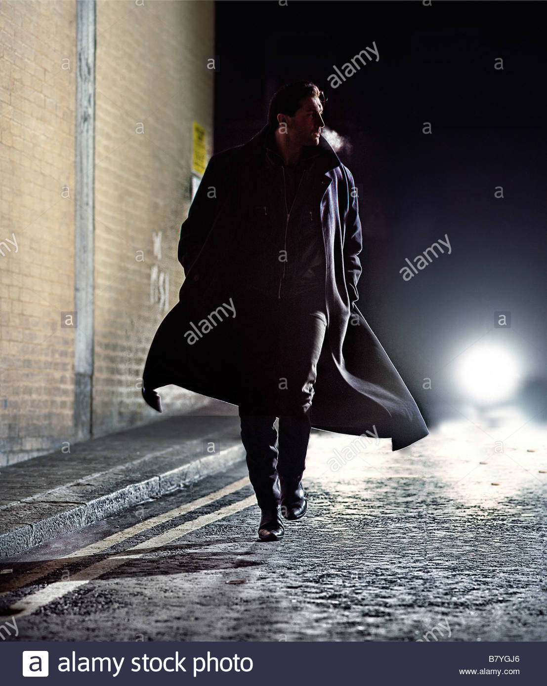 man in overcoat running down street at night - car lights behind Stock Foto