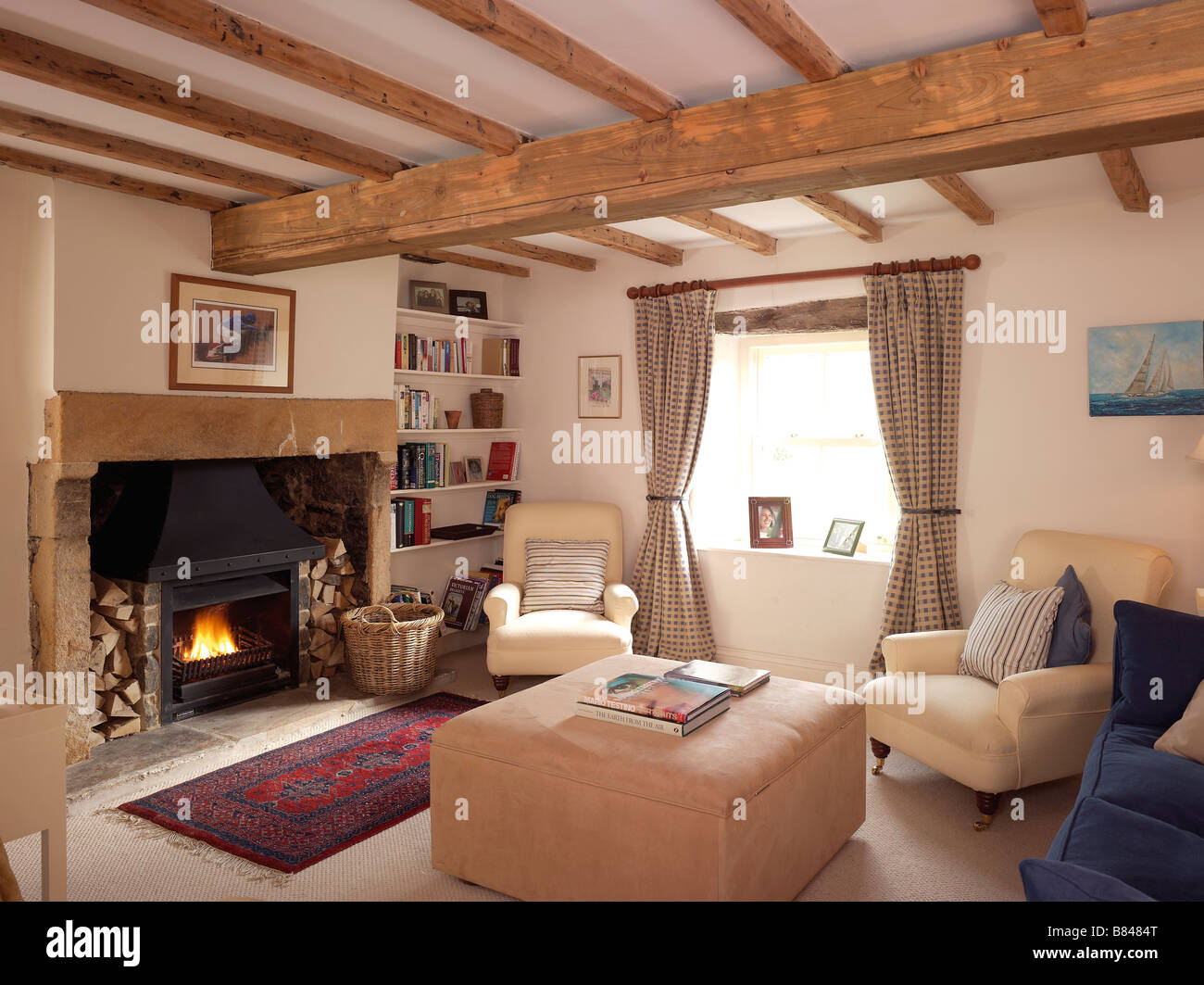 Country style living room with lit open fire and cream for Braunes sofa