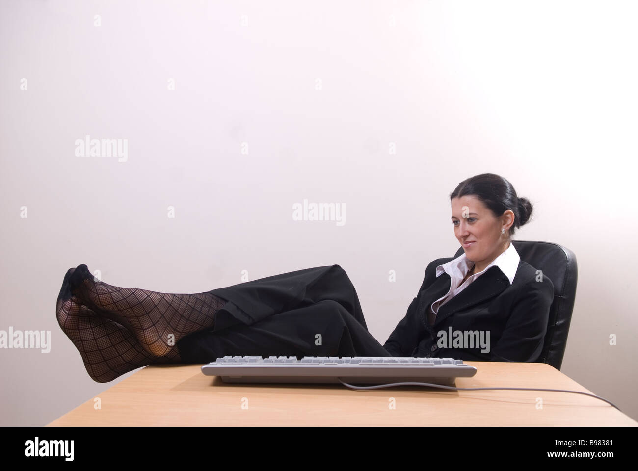 Business Woman Sitting In Office Feet On Desk Stock Photo