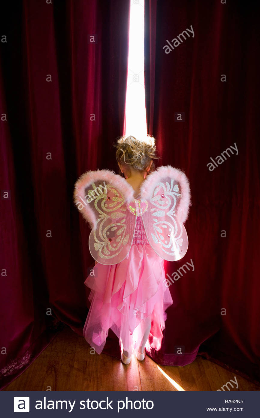 Girl (4-6) with fairy wings looking out gap in curtains, rear view Stock Foto
